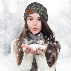 Winter portrait. Young, beautiful woman blowing snow